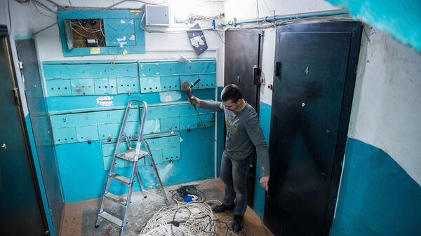Рабочие регионального фонда капитального ремонта многоквартирных домов меняют электропроводку в подъезде жилого дома в Омске