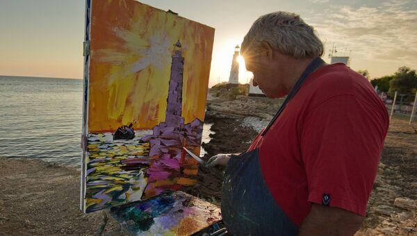 Художник пишет картину на берегу Черного моря вблизи маяка на мысе Тарханкут в Крыму