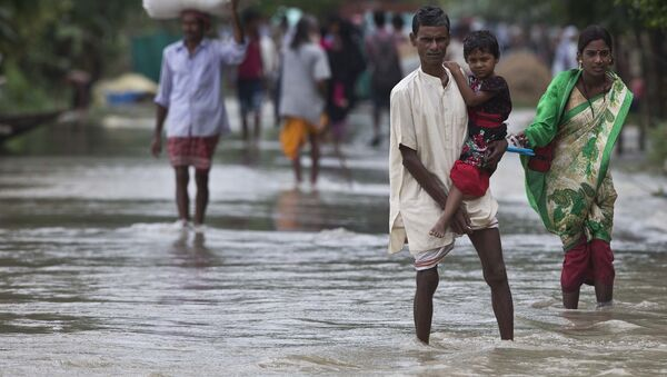 Люди во время наводнения в деревне Мурката к востоку от Гаухати в Индии. Архивное фото