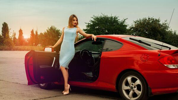 Девушка на высоких каблуках возле красной машины