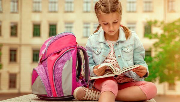 Школьница читает учебник