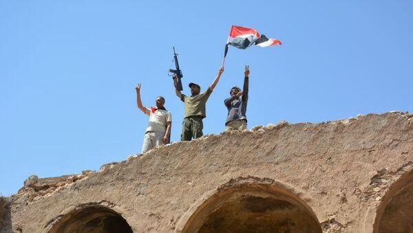 Мужчины с автоматом и Иракским флагом в городе Талль-Афар. 29 августа 2017