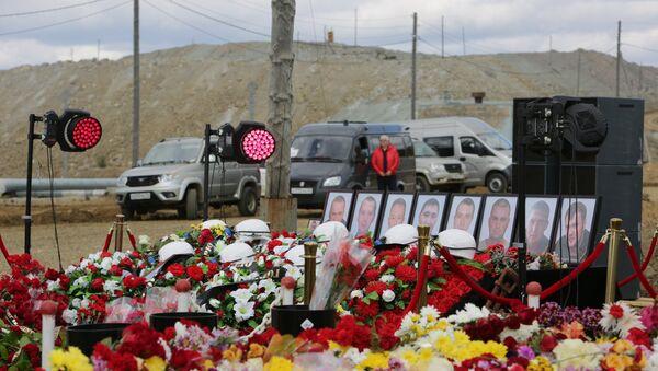 Цветы и свечи у памятного камня рядом со зданием администрации рудника Мир. 29 августа 2017