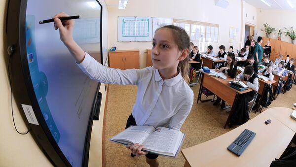Ученица выполняет задание возле интерактивной доски во время урока в московской школе. Архивное фото