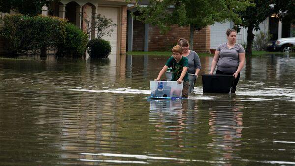 Местные жители с вещами на улице затопленной штормом Харви на северо-востоке Хьюстона. 30 августа 2017