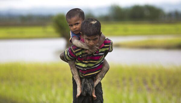Мальчик из народности рохинджа несет на спине ребенка после перехода бангладешской границы. 1 сентября 2017