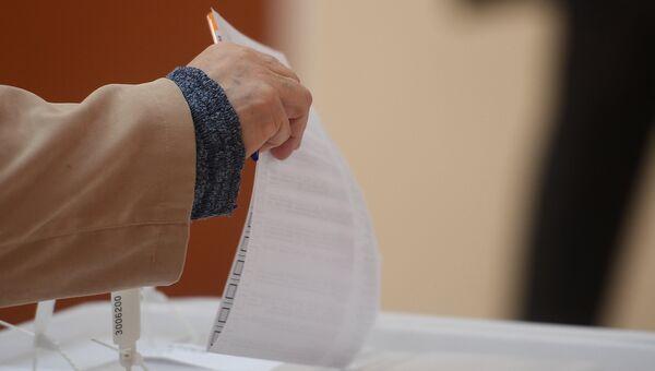 Избиратель кидает бюллетень в урну в единый день голосования. Архивное фото
