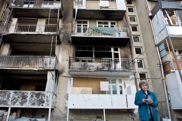 Жительница Цхинвали возле своего дома, пострадавшего от пуль и снарядов в ходе обстрелов города