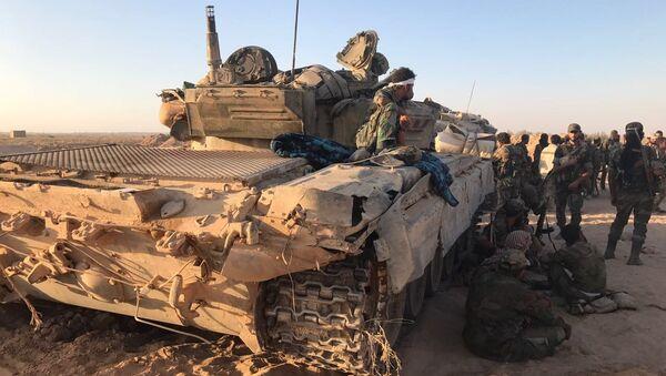 Бойцы сирийской армии отдыхают в тени техники на позициях в районе Дейр-эз-Зора. 15 сентября 2017