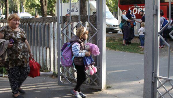 Женщина с ребенком у здания Республиканской клинической больницы в Донецке перед отправкой на лечение в Россию. 19 сентября 2017
