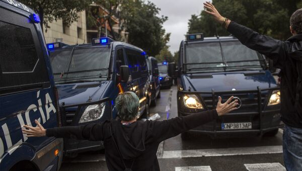 Люди пытаются остановить испанские полицейские фургоны в Барселоне, Испания. 1 октября 2017