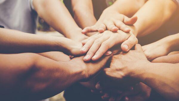 Группа людей держится за руки. Архивное фото