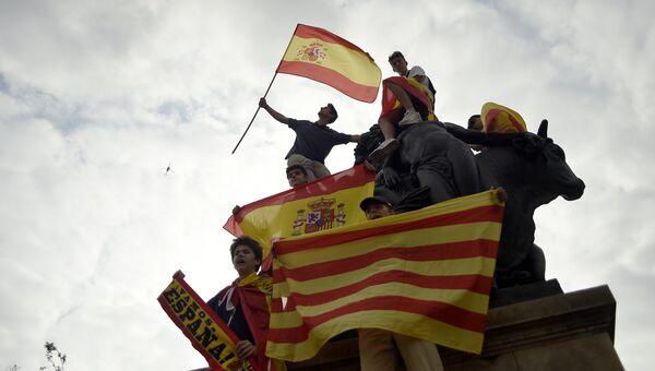 Протестующие с флагами Испании и Каталонии во время демонстрации в Национальный день Испании в Барселоне