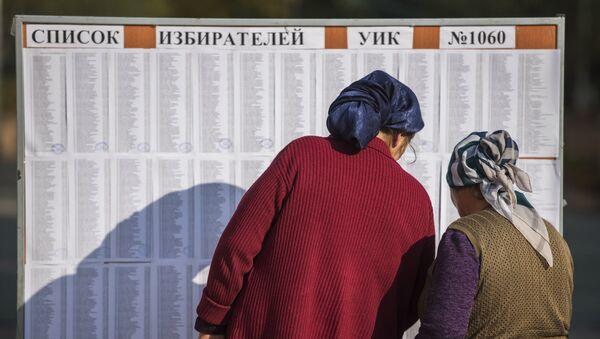 Женщины ищут свои фамилии в списке избирателей на избирательном участке в Бишкеке, чтобы проголосовать на выборах президента Киргизии. 15 октября 2017