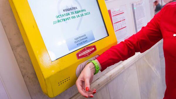 Пассажир московского метро проверяет счет электронного кошелька транспортной карты Тройка с помощью силиконового браслета