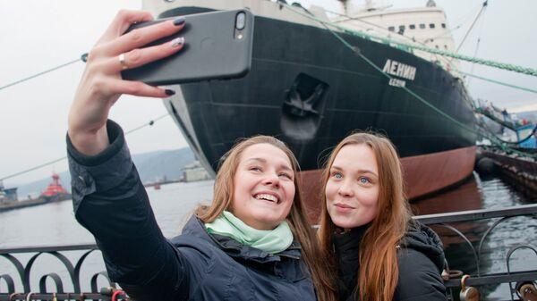 Девушки фотографируются перед музеем-ледоколом Ленин в Мурманске