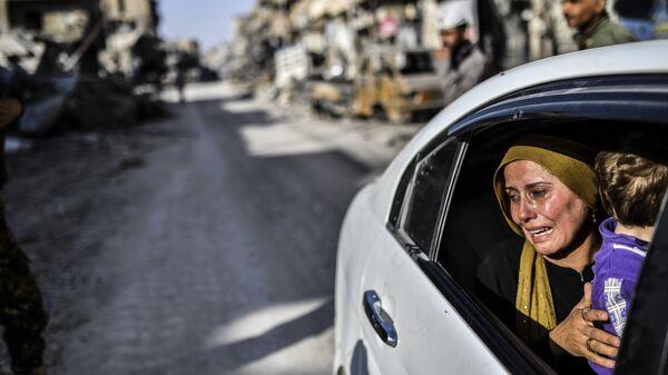 Женщина с ребенком плачет, глядя на свой дом в Ракке, Сирия