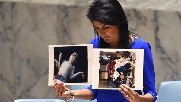 Постпред США при ООН Никки Хейли держит фотографии жертв предполагаемой химической атаки в Сирии