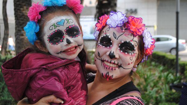 Мама с дочерью, участвующие в параде в честь дня мертвых