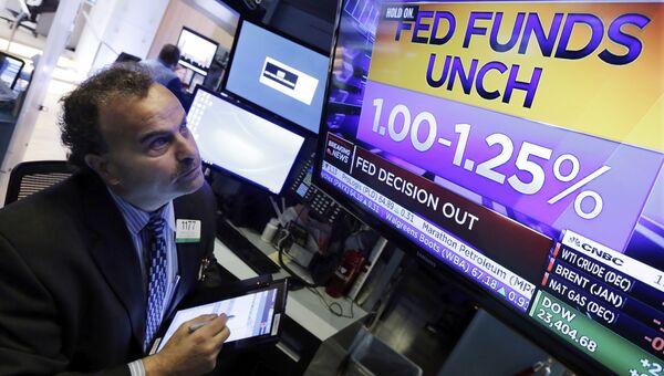 Трейдер смотрит на табло, на котором отображается решение ФРС относительно изменения процентной ставки на Нью-Йоркской фондовой бирже. 1 ноября 2017