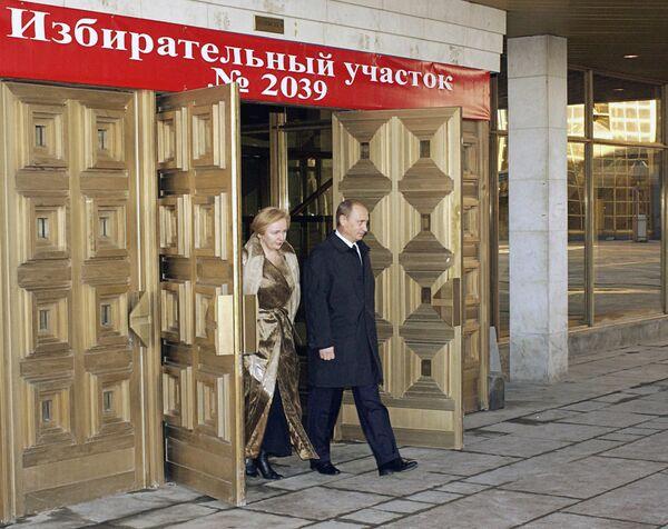 Президент РФ Владимир Путин и его супруга Людмила Путина после голосования на выборах президента Российской Федерации выходят из избирательного участка №2039