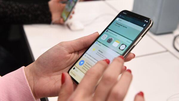 Покупатели рассматривают новый смартфон iPhone X в магазине. Архивное фото
