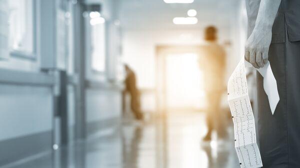 Врач с результатом кардиограммы в коридоре больницы