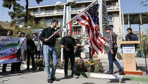 Студенты жгут флаг США во время протестов в Тегеране, Иран