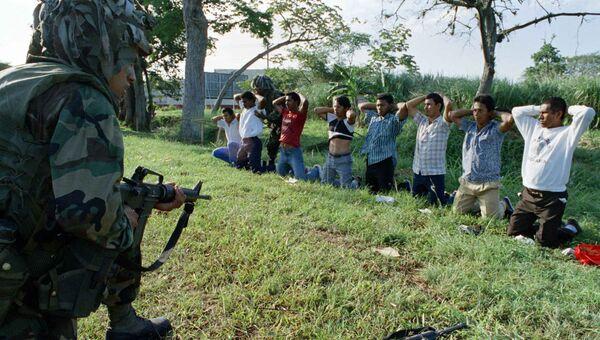 Американский солдат охраняет группу задержанных панамцев. 27 декабря 1989