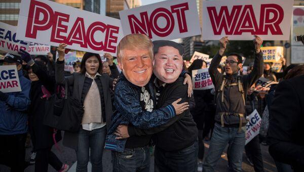 Демонстранты в масках, изображающих Дональда Трампа и Ким Чен Ына. Архивное фото
