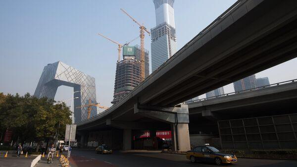 Слева - штаб-квартира центрального китайского телевидения CCTV в Пекине
