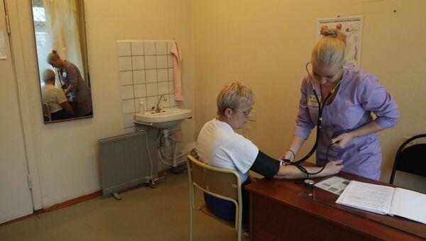 Наталья Флеглер осматривает пациентку. Заостровская участковая больница, Архангельская область