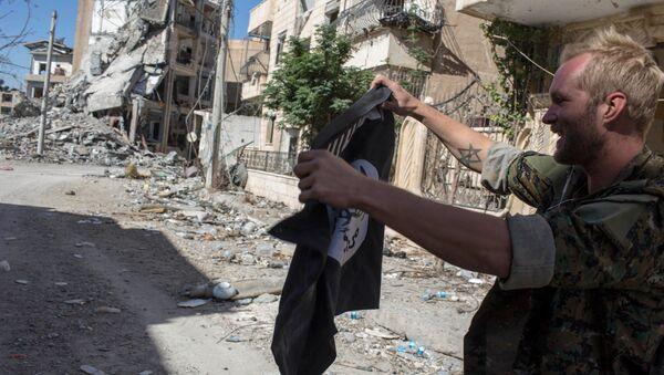 Мужчина в военной форме держит флаг ИГ (террористическая организация, запрещена в РФ) в Ракке. Архивное фото
