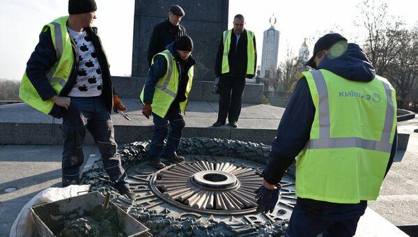 Работники Киевгаз о время работ по очищению вновь залитого цементом мемориала Вечный огонь в парке Славы в Киеве. 20 ноября 2017