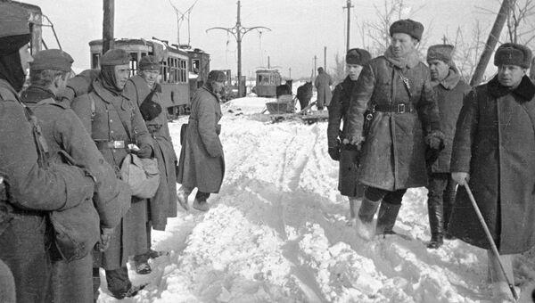 Советские офицеры проходят мимо немецких пленных. Сталинград, январь 1943 года