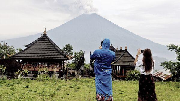 Туристы фотографируют извержение вулкана Агунг на острове Бали, Индонезия. 29 ноября 2017