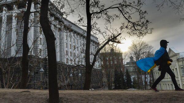 Мужчина с флагом Украины у здания правительства в Киеве. Архивное фото