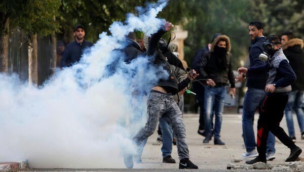 Палестинский протестующий бросает баллон со слезоточивым газом в сторону израильских военныз во время столкновений в Вифлееме на Западном берегу. 7 декабря 2017