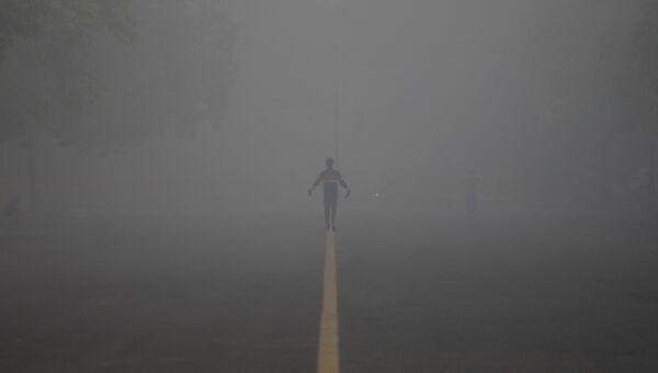 Человек на дороге, накрытой туманом, в Нью-Дели, Индия. 21 декабря 2017
