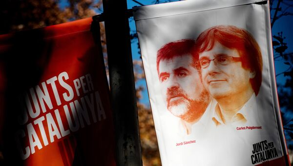 Предвыборный баннер с изображением бывшего председателя правительства Каталонии Карлеса Пучдемона и лидера Национальной ассоциация Каталонии Жорди Санчеса в Барселоне. 21 декабря 2017