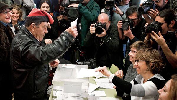 Мужчина голосует на избирательном участке на внеочередных выборах в парламент Каталонии