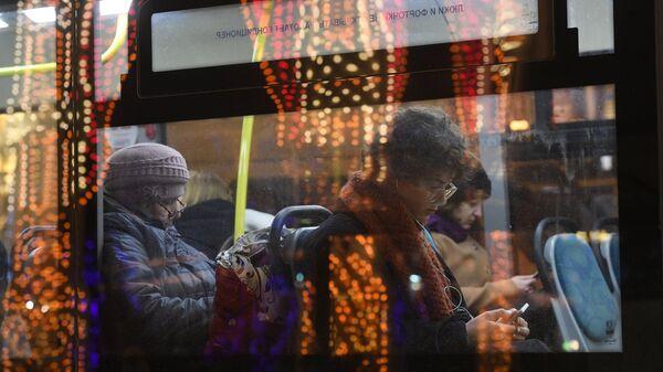 Пассажиры в салоне автобуса, проезжающего мимо Театральной площади в Москве