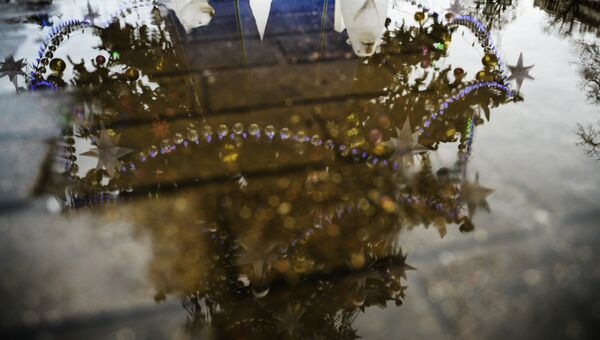 Отражение в луже новогодней елки. Архивное фото