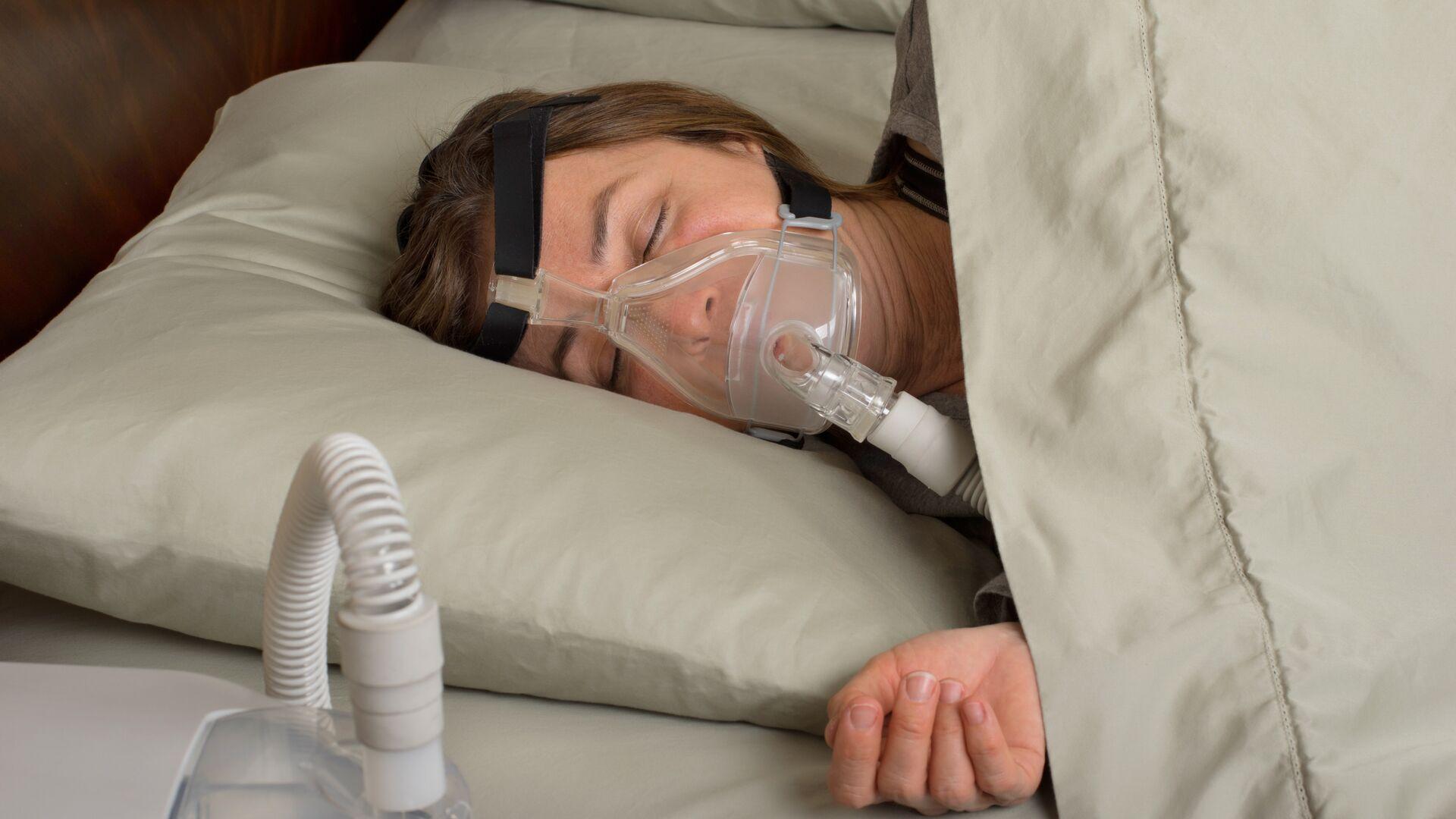 Женщина спит с аппаратом, препятствующим остановке дыхания - РИА Новости, 1920, 25.12.2020