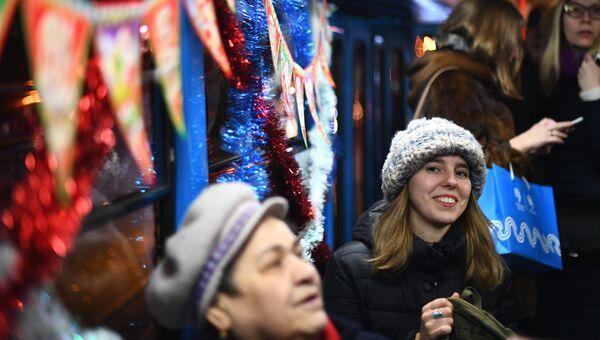 Пассажиры в салоне новогоднего трамвая в Москве