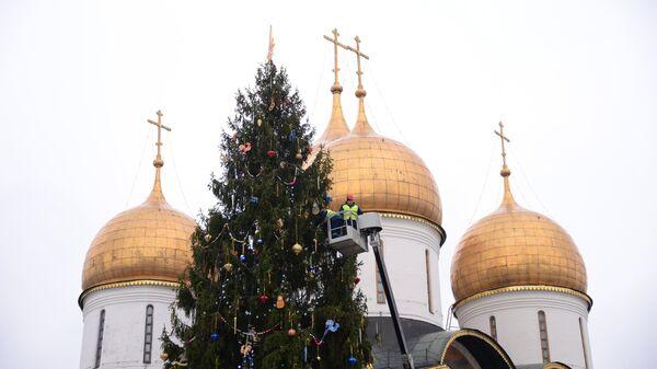 Рабочие украшают новогоднюю елку на Соборной площади Кремля