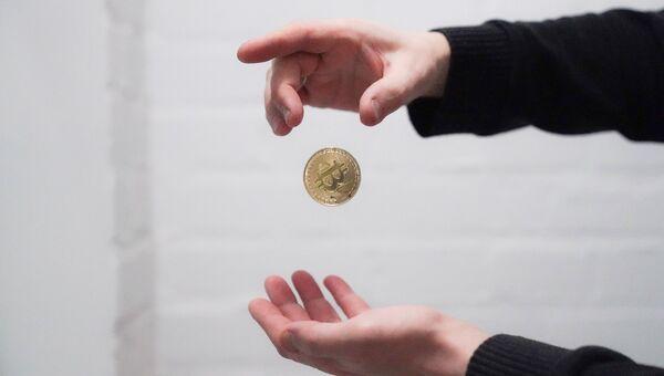 Сувенирная монета с логотипом криптовалюты биткоин. Архивное фото