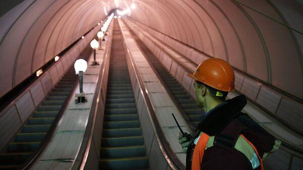 Рабочий у эскалатора строящейся станции московского метро Окружная