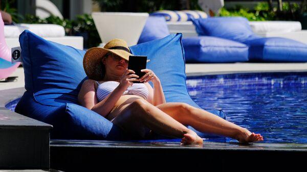 Девушка отдыхает у бассейна на территории отеля в Таиланде