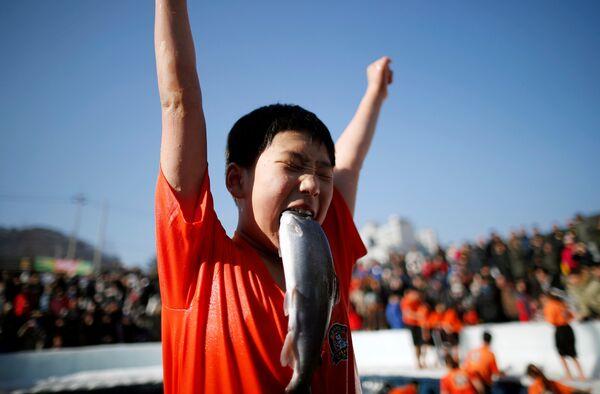 Мальчик радуется пойманной собственными руками форели во время мероприятия, посвященного ледовому фестивалю, в Хвачеоне, Южная Корея